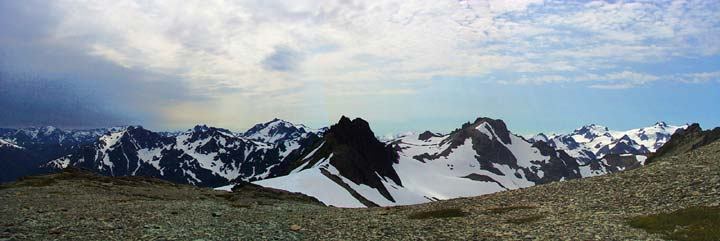 Panoramic of jagged snow-covered peaks.
