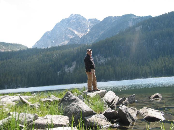 An Americorps volunteer poses atop a rock near the edge of Carp Lake in the Anaconda Pintler Wilderness.