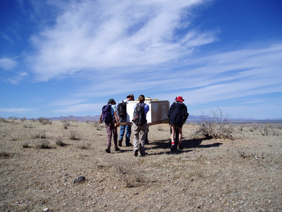 A group of people carry a refrigerator out of the wilderness on a litter.  The sky is a rich shade of blue, and sandy ground is beneath their feet.