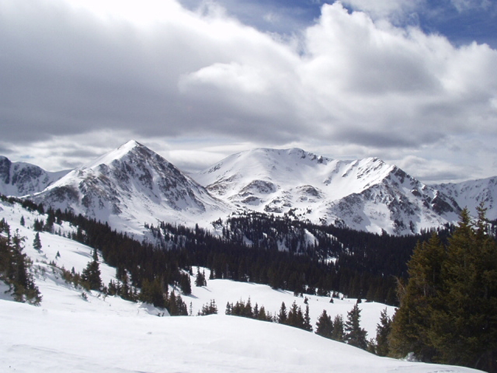 Baker Pass in winter where the landscape if blanketed in snow and the sky is grey.