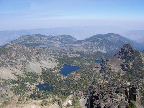 From an aerial view, you can see three lakes and a series of tall, rocky peaks and rock formations.