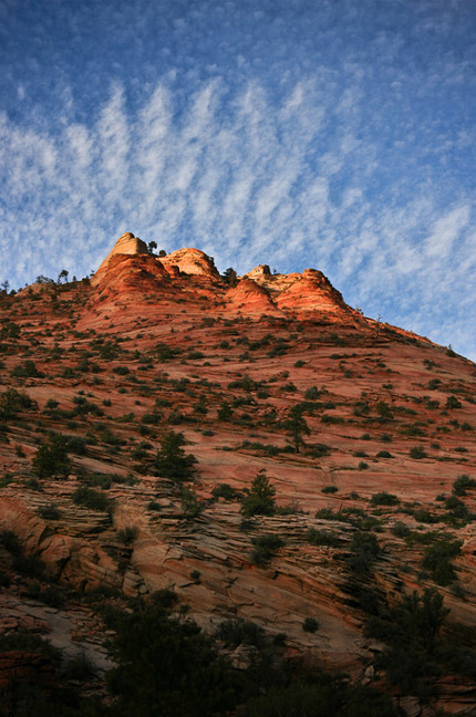 A mountainous, deep red rock formation is dotted with shrubs and other plant life as the sun casts its rays only on the peak of the moutain.