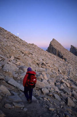 A hiker in red gear watches the horizon change colors during the evening dusk.