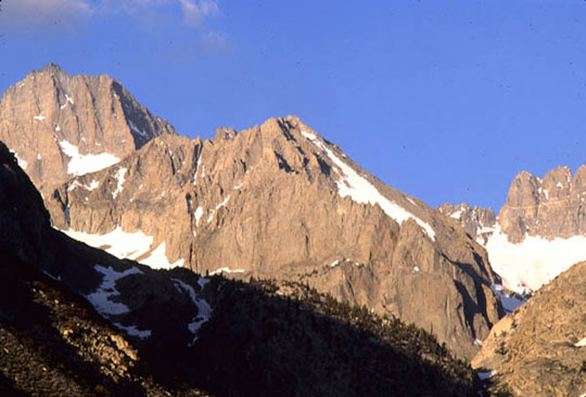 The Palisade Mountain peaks are dotted with snow as the sun casts glowing, warm rays on the peaks.