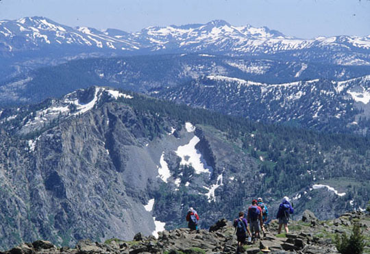 Hikers stand atop the Mt. Tallac Trail and gaze out at the vast mountains roll out across the land, patched with snow.