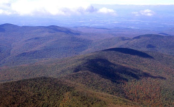 Aerial view of Romance Mountain where autumn trees are in transition from green to red and yellow. The clouds cast shadows over land.