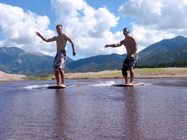 Two young men skimboarding across the shallow water with sand dunes and mountains rising in the background.