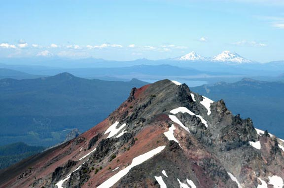The summit of Diamond Peak is streaked with red dirt and patches of snow sit idely amidst the craigs.
