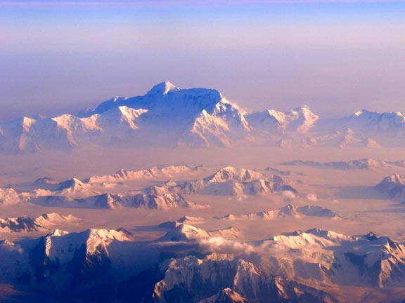 An iconic scene of a jagged ice capped peak, rising above an icefield dotted with mountain ridges, and bathed in a pink haze of morning light.