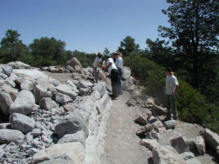 A group of workers traverse a wall of rocks.