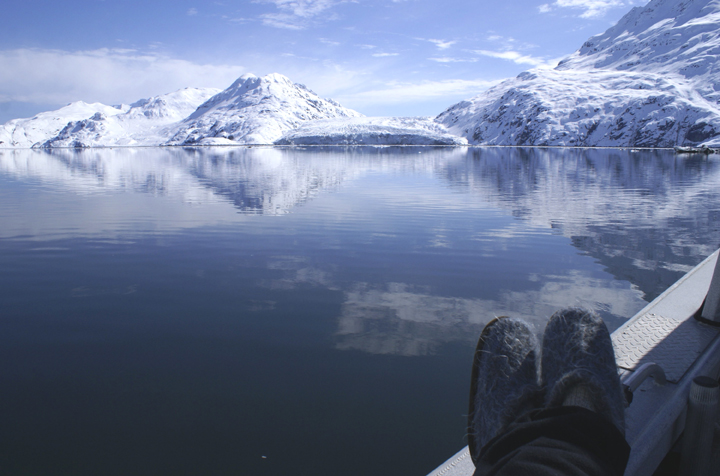 The photographer's two fuzzy slippers rest on the edge of a boat.  Beyond is water, in which the reflection of the massive glaciers above can be seen.