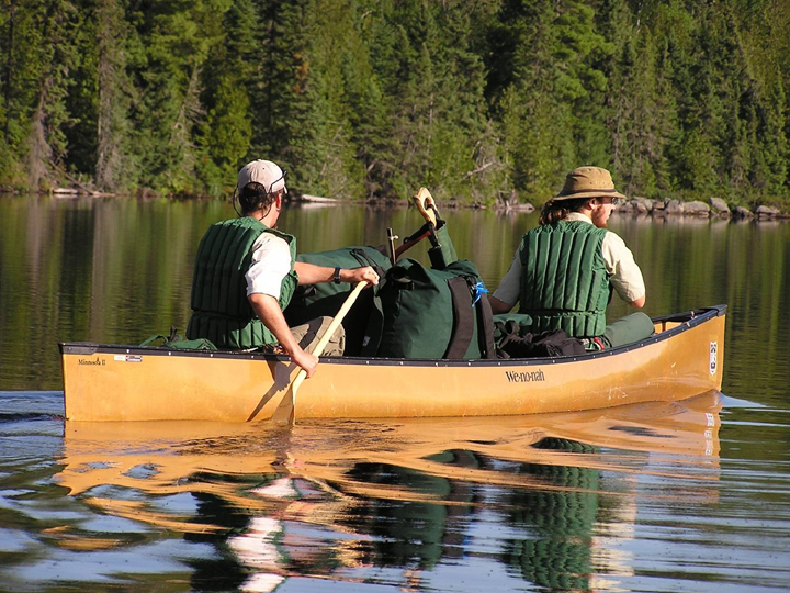 Two Wilderness Rangers in a yellow canoe filled with camping gear paddle across a tranquil lake.