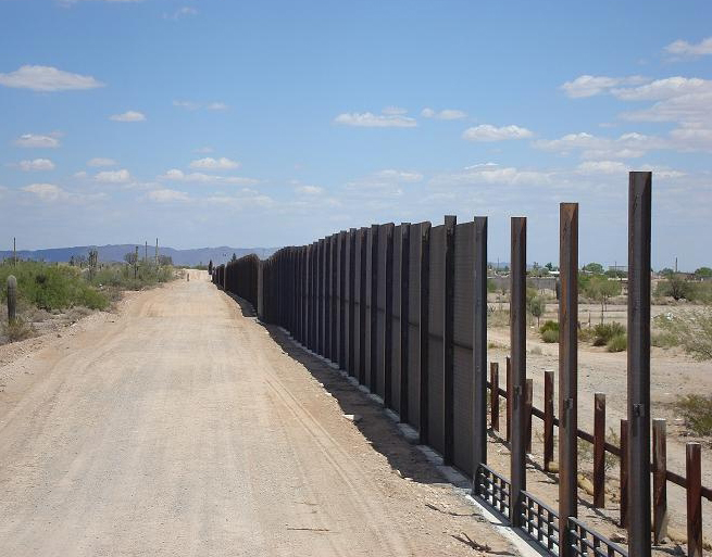 Fenceposts stretch down a dusty road, refleting the partially completed nature of the U.S. - Mexico border fence.