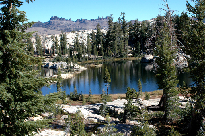Powell Lake with Three Chimneys in the background. Few trees populate the area surrounding the little lake while white rocks also inhabit the area.