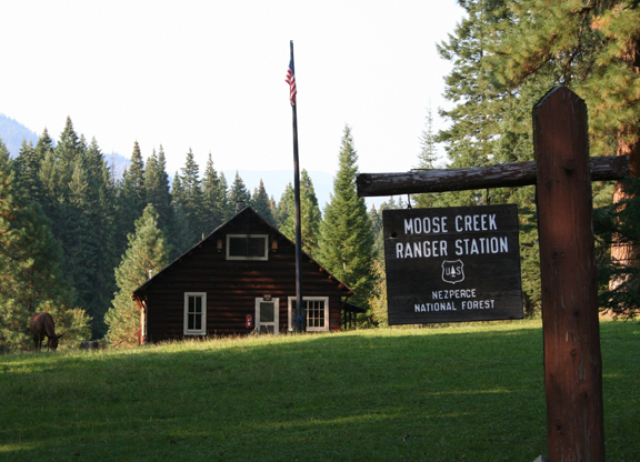 A photo of the cabin that is the Moose Creek Ranger Station and a sign off to the right that reads
