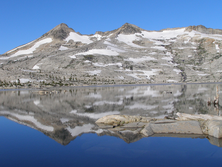 A cold, desolate looking peak is reflected in the still waters of a beautiful blue lake.