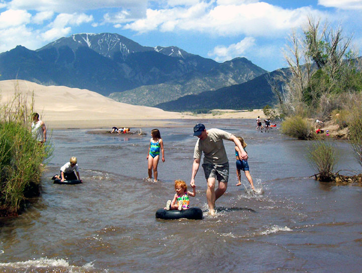 Young children in inner tubes and adults play in shallow water with golden dunes and mountains rising in the background.