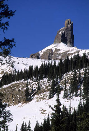 A striking outcropping, known as Lizardhead Peak stands in the distance, jutting up out of the mountain. Snow blankets the area as the sky opens up in a deep, dark blue fashion.