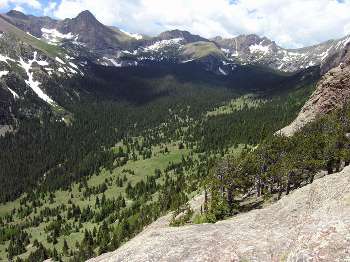 A high forested green mountain valley leads up to rocky faces laced with snow.