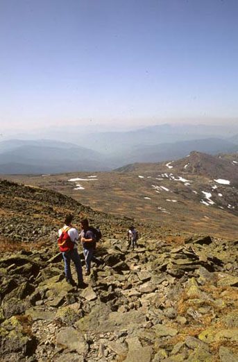 Three hikers climb up a rocky mountain side on a hazy, sunny day.