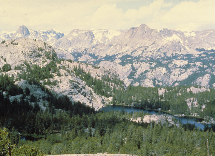 Looking down into the valley, tall trees pop up around rock formations and a single blue lake.
