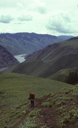 A backpacker hikes along a trail amidst rolling green hills, while clouds darken and grow large, blotting out the sun.