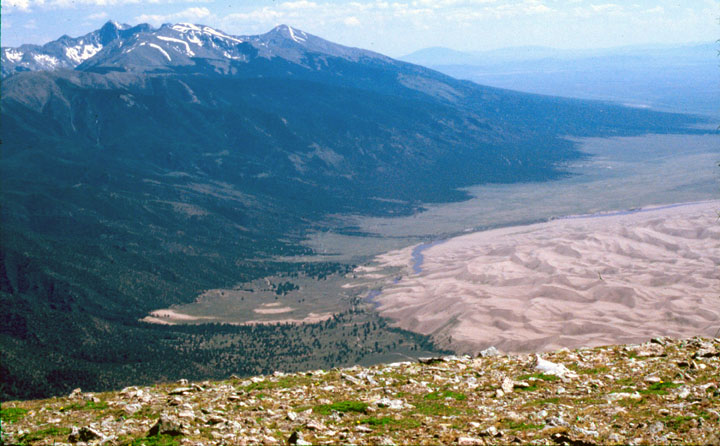 A view from far above the valley. High mountains in the distance ead down to textured sand dunes on the valley floor.