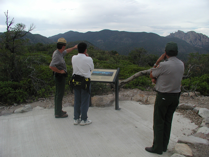 Two uniformed staff members talk with a visitor at aa stone viewpoint overlooking a vast forested valley.