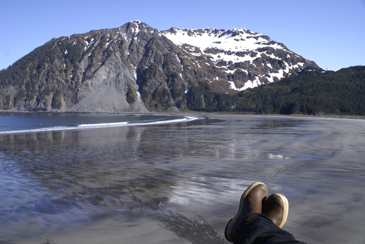 The photographer's two boots can be seen in the sand, resting just above the high tide line.  The ocean is down in the background, and beyond it rises the sheer majesty of a snow laden mountain.