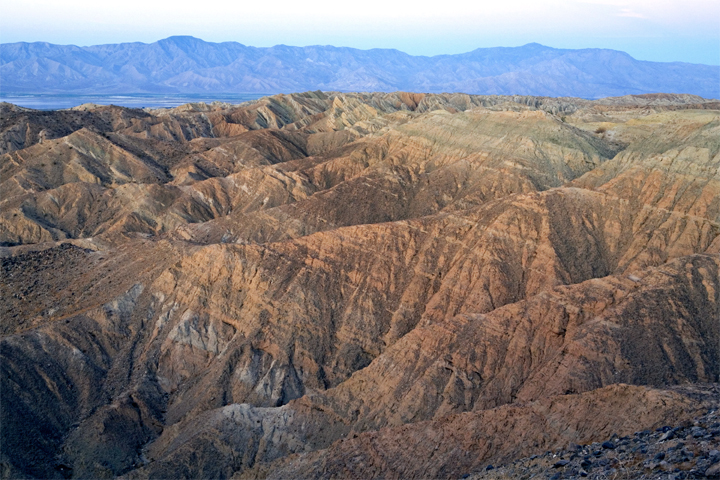 Red and orange ridges show off their stratigraphy lines beneath a faded blue sky.