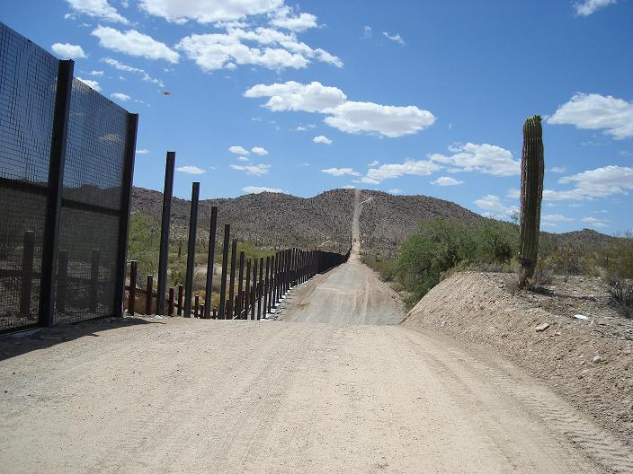 A road stretches into the distance, marked off on one side by the skeleton of the half built U.S. - Mexico border fence.