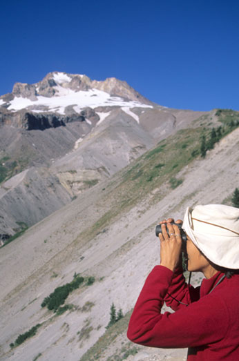 A woman looks through her binoculars scanning for wildlife by Zig Zag Canyon.