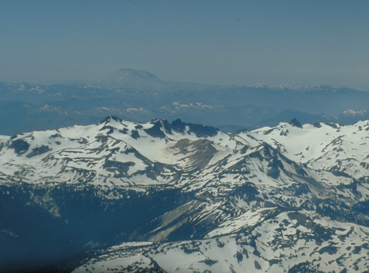 Snow laden peaks dominate the vista, nearly hiding the forested valley on the left of the shot.