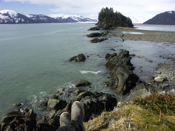 The photographer's two boots are seen in the foreground at he looks out onto a small inslet of ocean.  There is a tree-covered island a ways out, and beyond the blue water is a series of snow capped mountains.