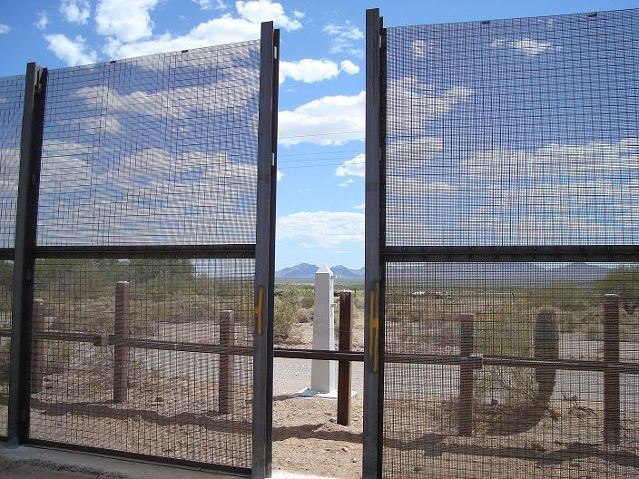 A gap in a massive black U.S. - Mexico border fence can be seen.