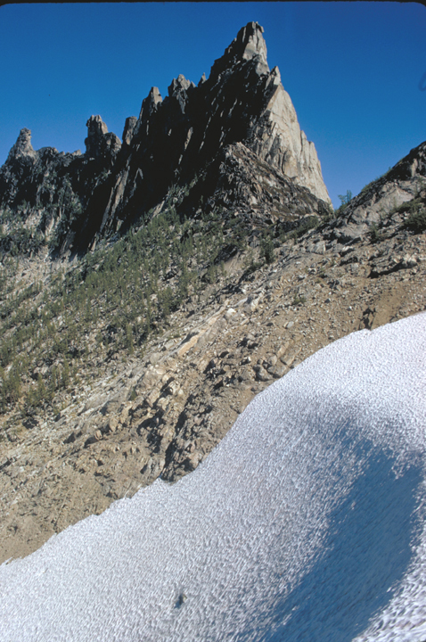 A sheer cliff rises above its compatriots.  Snow dominates the foreground.