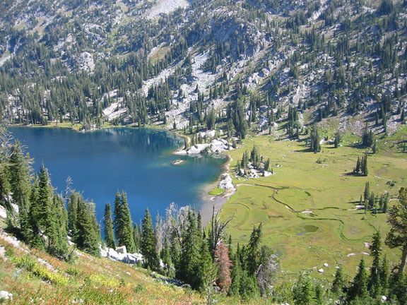 From the upper part of a valley looking down, a gloriously blue lake can be seen amid the greenery of a lush valley.