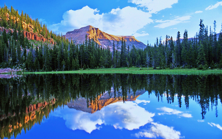A mountain peak rises in the distance with blue sky parted by white clouds above all perfectly mirrored in a glassy smooth lake.