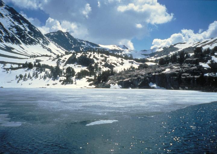 Snowy peaks rise over a semi-frozen lake.