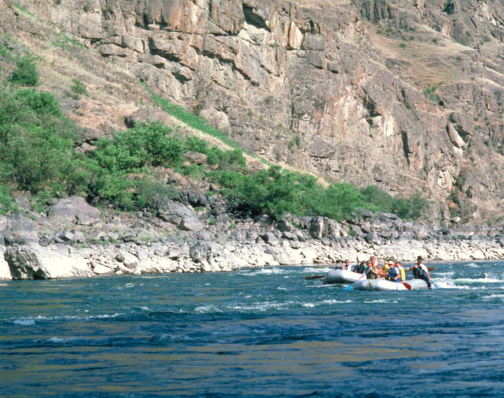 Three small rafts challenge a river, sliding through the blue waters against a backdrop of one massive stony cliff.