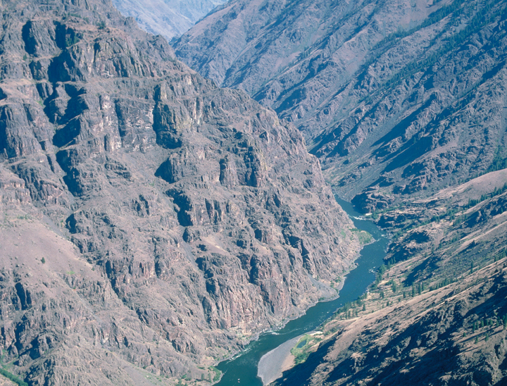 A tiered brown canyon rises up from a low river bed.  The blue water snakes far below from an almost aerial perspective.
