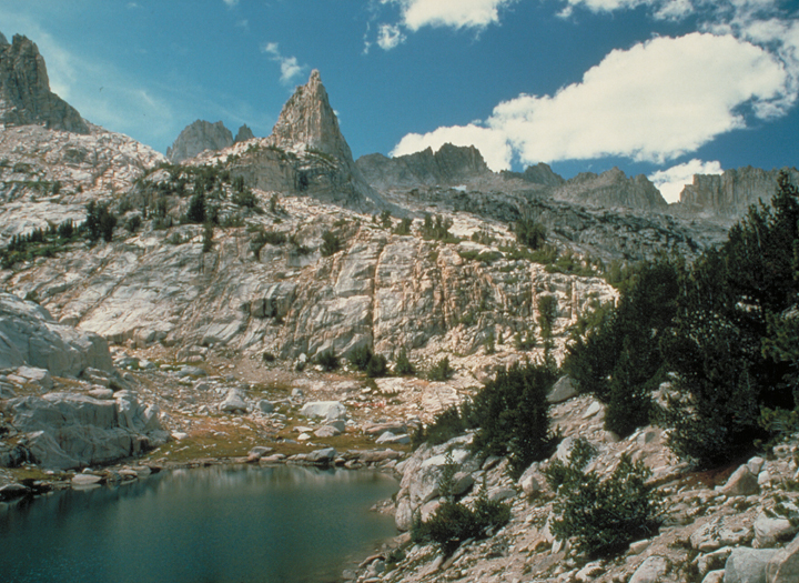 A lake is situated between a series of rocky precipices.  A few trees litter the slopes.