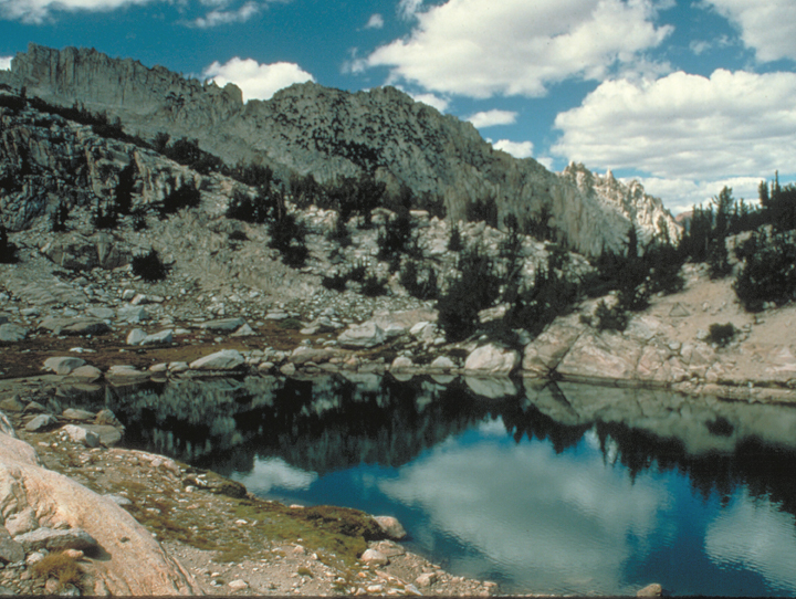 The surface of the lake reflects its surroundings of massive grey cliffs and scattered green trees.