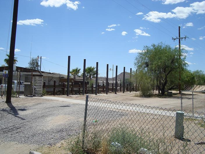 The U.S. - Mexico border fence skeleton can be seen, as well as powerlines and a small building.