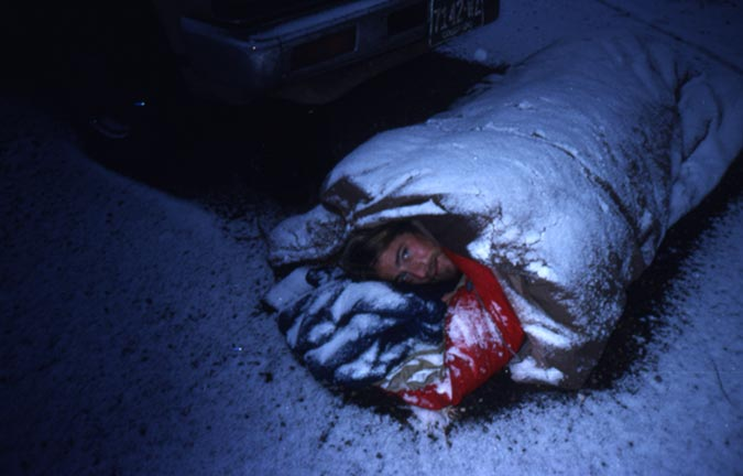 A man poking his head out of a sleeping bag rolled in a large tarp, covered in a thin layer of snow.