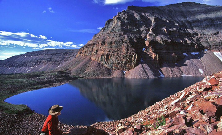 A single hiker looks over a smooth lake reflecting a mountain peak and the blue sky above.