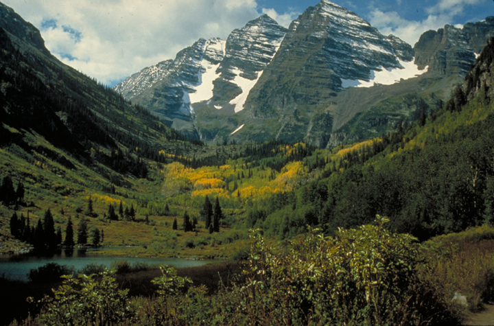 The valley is pure majesty, overshadowed by a still snowy cliff and flourishing below with golden and green grasses.  The lake and trees complete the perfect scene.