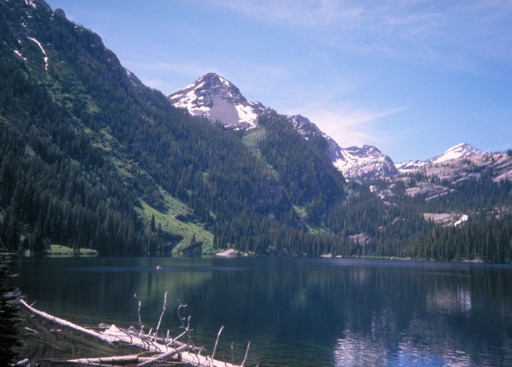 The mountainsides surrounding the lake are covered with trees and the occasional strip of green grass.  The peaks are still dotted with snow.
