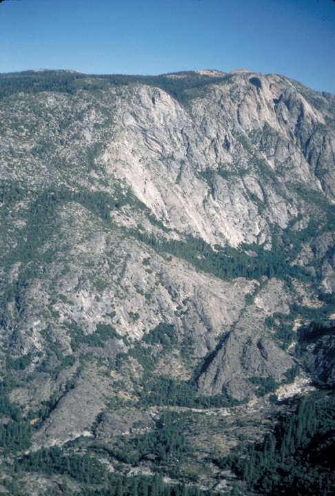 The portait shows a valley, focusing mainly on the far wall which is a strange conglomeration of vertical sheers, hills and the occasional line of trees.