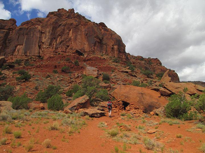 Backpacker below red cliffs.